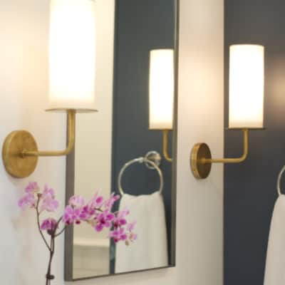 brass wall sconces flanking mirror in hall bathroom remodel