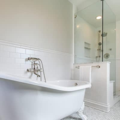 cast iron free standing bath tub next to large walk in shower