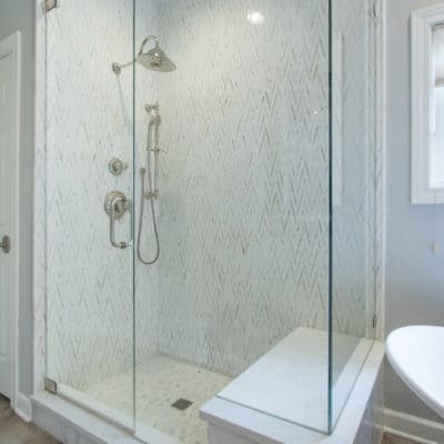 custom shower featuring marble tile and polished nickel faucets