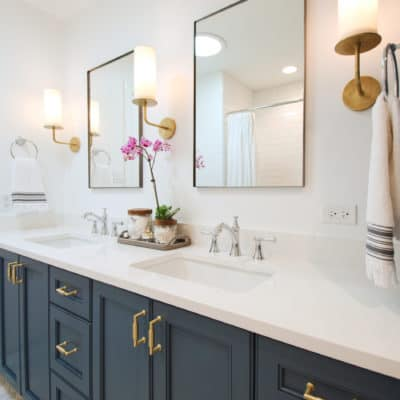 painted blue vanity with mirrors and sconces