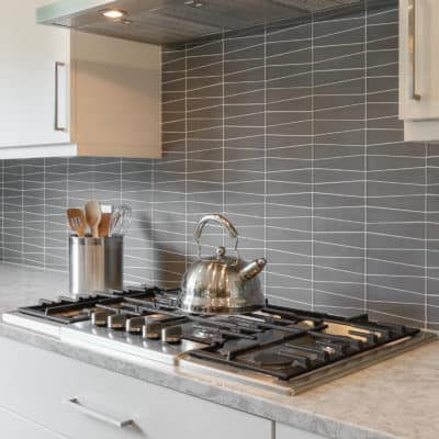 glass tile backsplash behind cooktop in kitchen